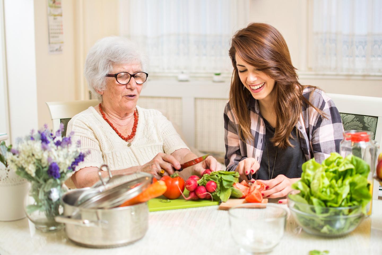 Grandmother and granddaughter preparing food at home.