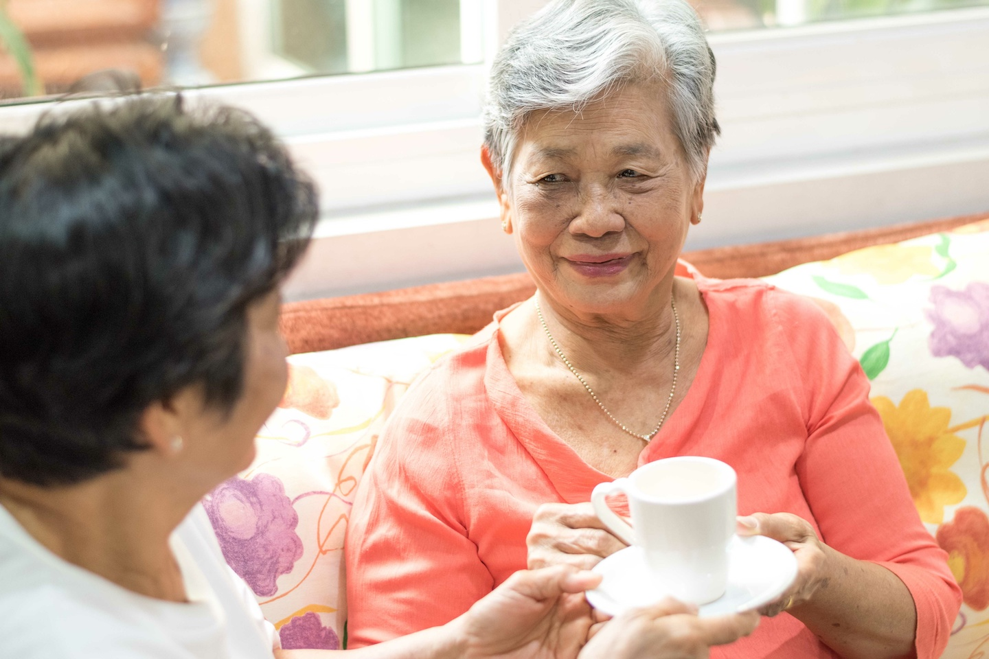 Happy senior freindship society concept. Portrait of Asian female older ageing women smiling with happiness serving hot tea taking care each other at home,nursing home, or wellbeing county